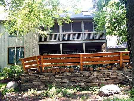 Curved stacked stone curved wall with cedar railing